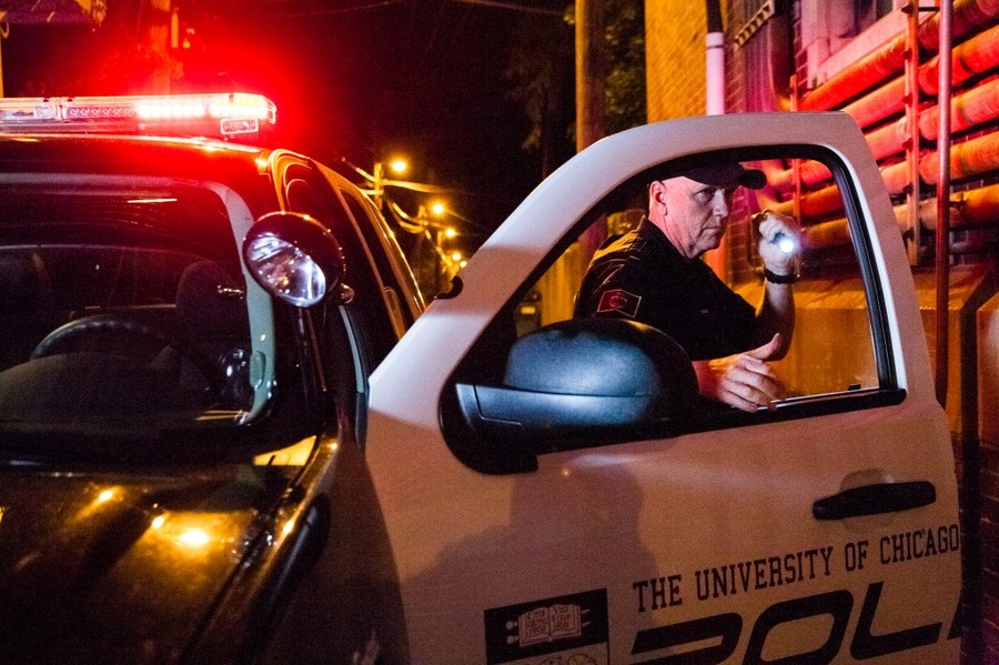 A UCPD officer shines his flashlight next to a UCPD squad car.