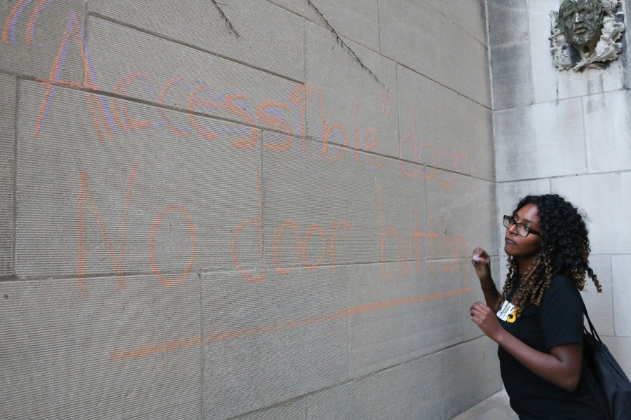 """Mariam Desta works on chalking a wall with the message: """"Accessible door—No door button"""" as part of a protest held a week ago."""