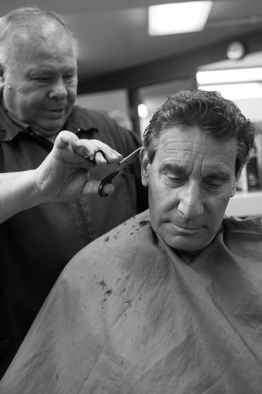 Sil Vigilante cuts a client's hair last year, prior to the closing of the barbershop in Reynolds Club.