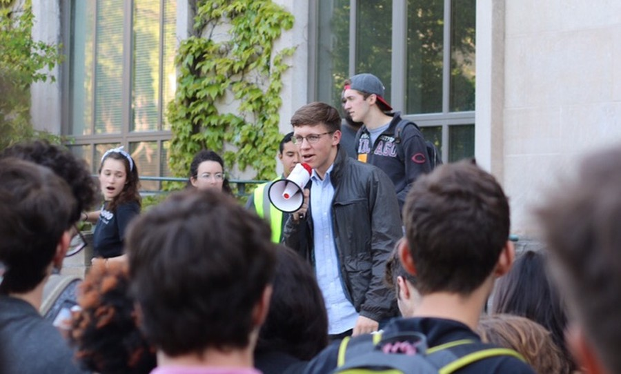 SG President Tyler Kissinger speaking over a megaphone at the May 19 rally outside Levi Hall.