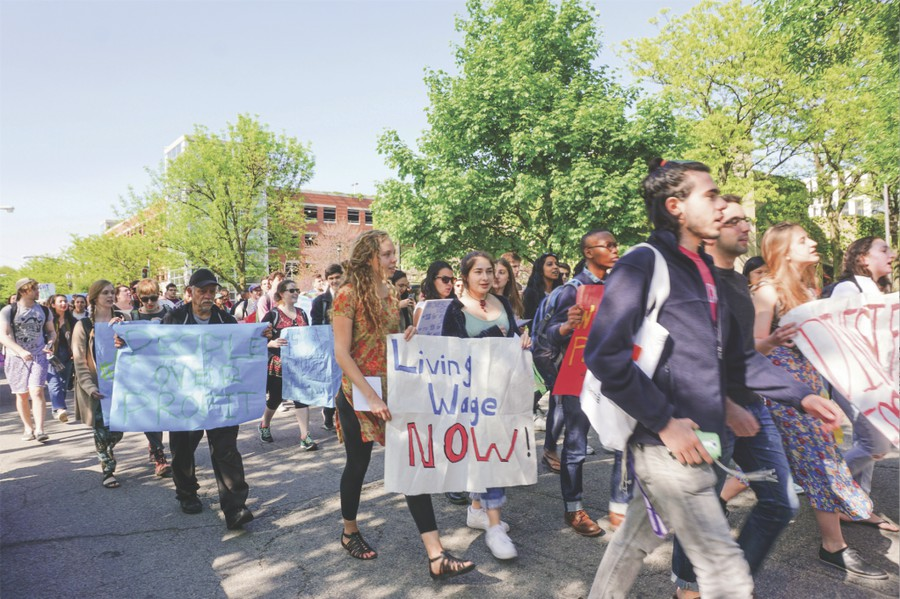 Students walk down the street during the protest to democratize the University holding various posters.
