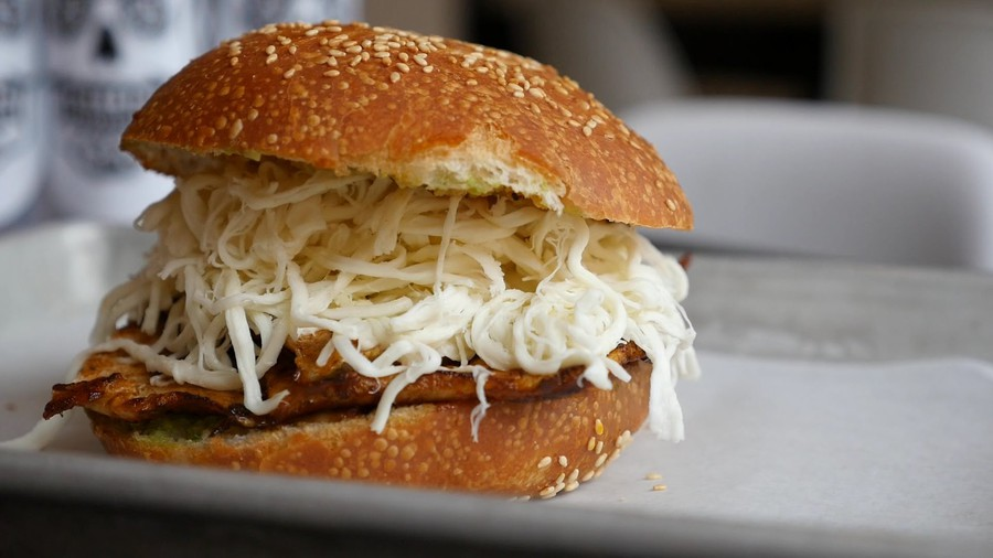 The cemita is served on sesame seed bread with Oaxacan cheese.