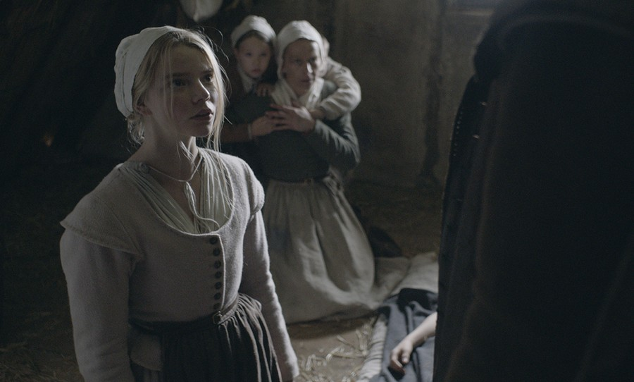 Teenage heroine Thomasin (Anya Taylor-Joy) stands before her cowering family.