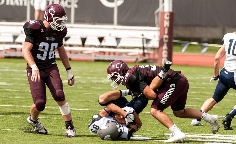 Fourh-year linebacker Hayden Harrow tackles a Case Western Reserve Spartan as second-year lineman Stash Rowley looks on.