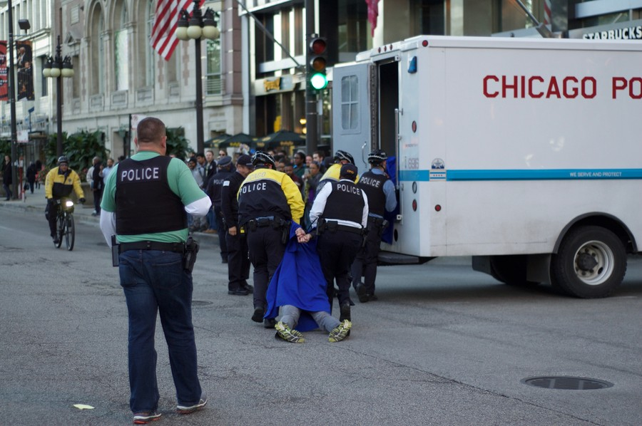 Chicago police carry a limp protestor in a cap and gown into a police van.