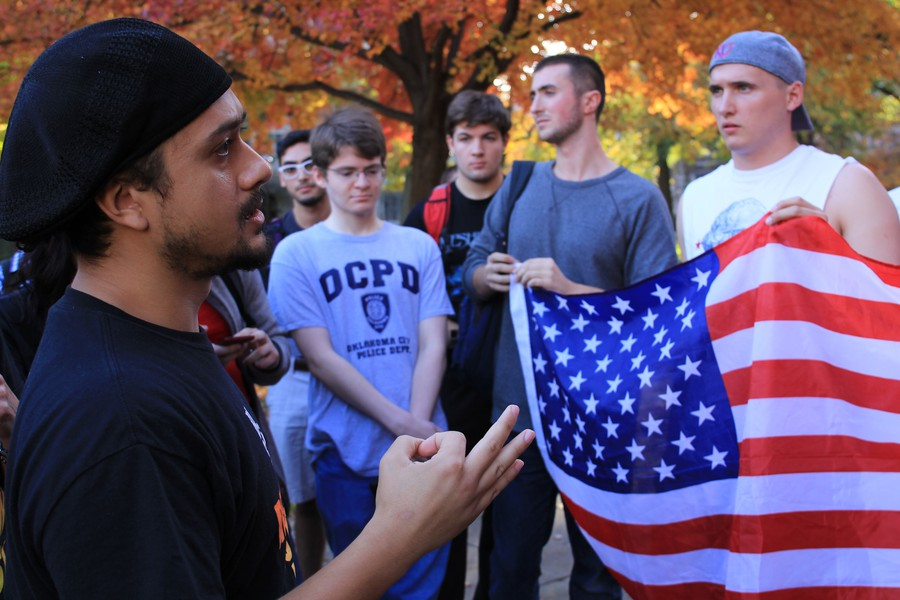 Students hold an American flag while banned Revolutionary Communist Party member Noche Diaz gives a talk on the quad.