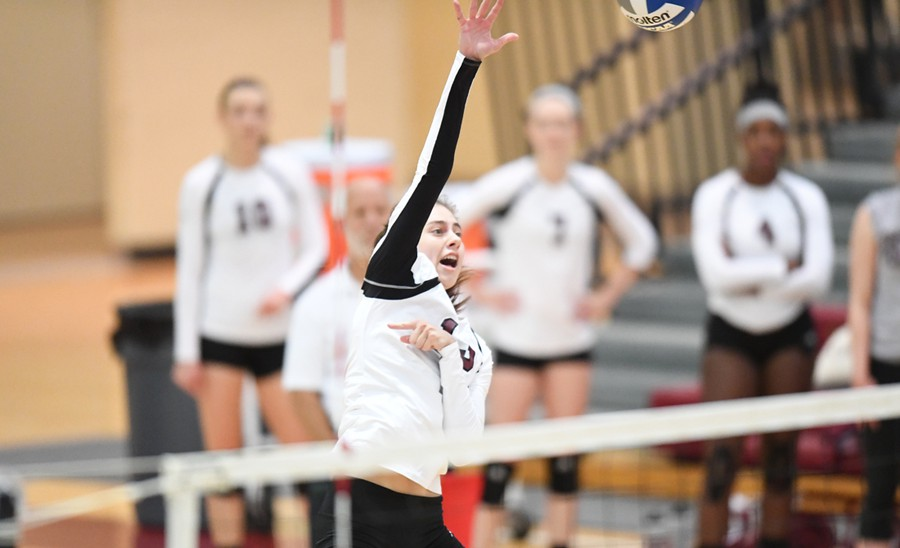 Second-year outside hitter Audrey Scrafford rises high above the net for to strike the ball.