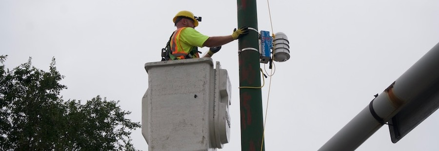 A worker installing one of the AoT sensors.