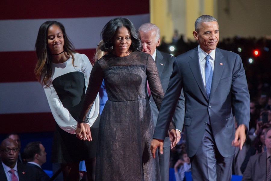 Obama leads his family onto stage, hand in hand.