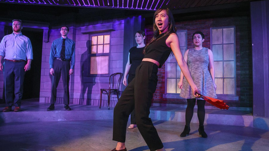 Tien Tran (center) and Numero Uno's ensemble deliver timely, if tired, laughs.