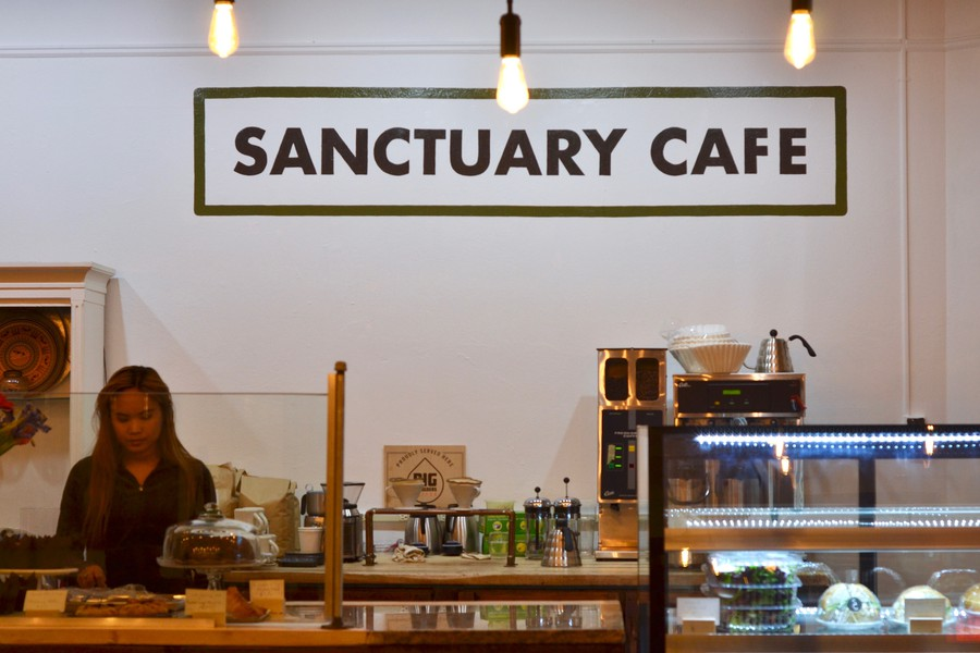 Baristas prepare coffee at the grand opening of Sanctuary Cafe.