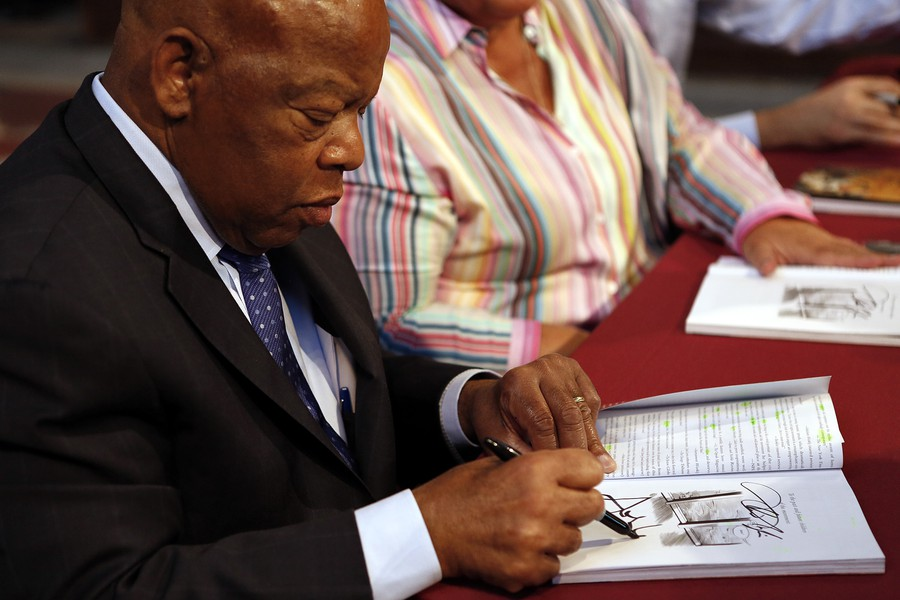Representative Lewis signing a copy of his new graphic novel.