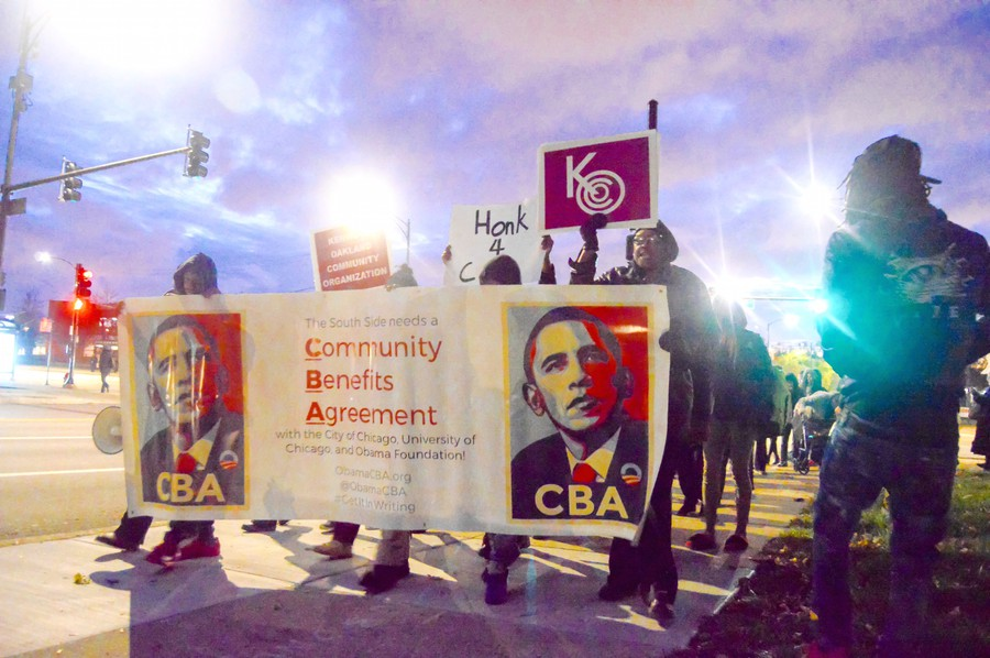 Protesters from the Obama Library South Side CBA Coalition hold signs on their march to Jackson Park.