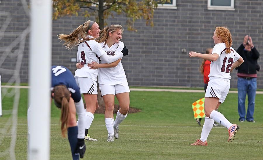 First-years Maddie Devoe and Katie Jasminski and third-year Jenna McKinney celebrate a goal.