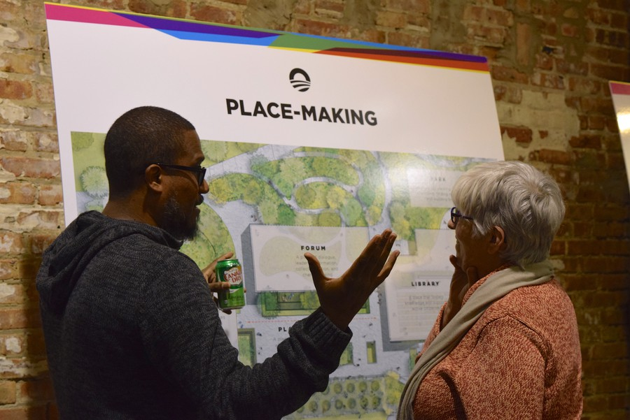 Two attendees review plans for the Obama Presidential Center.