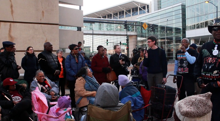 A UChicago Student speaks to community members at the prayer vigil against displacement outside the McCormick Center