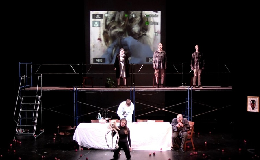 """The cast """"Broken Jug"""" performs on a minimally decorated stage, emphasizing the eerie and deadpan acting and narrative."""