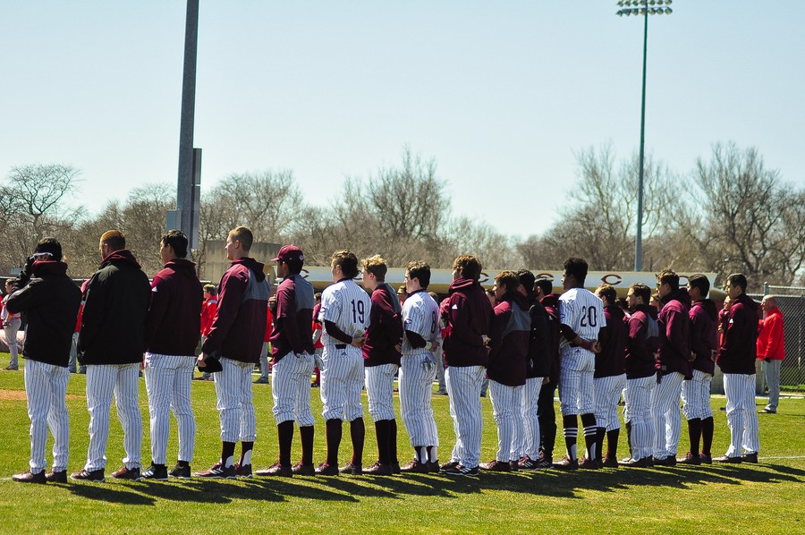 The Maroon baseball team looks on during the National Anthem.