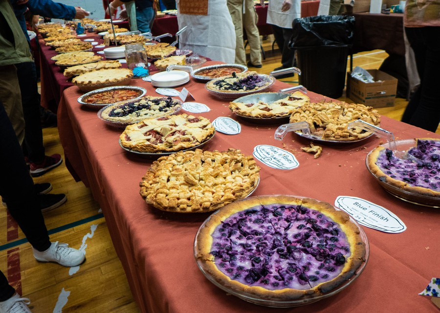Dozens of fruit pies line the table, sliced and ready for eating