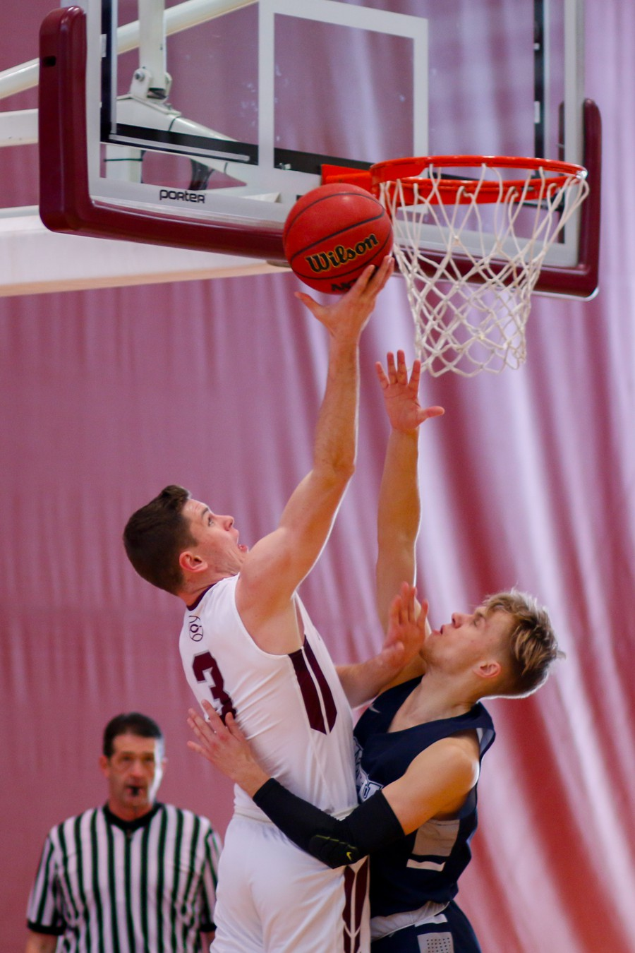 Third-year Cole Schmitz avoids his defender to tip the ball into the hoop.