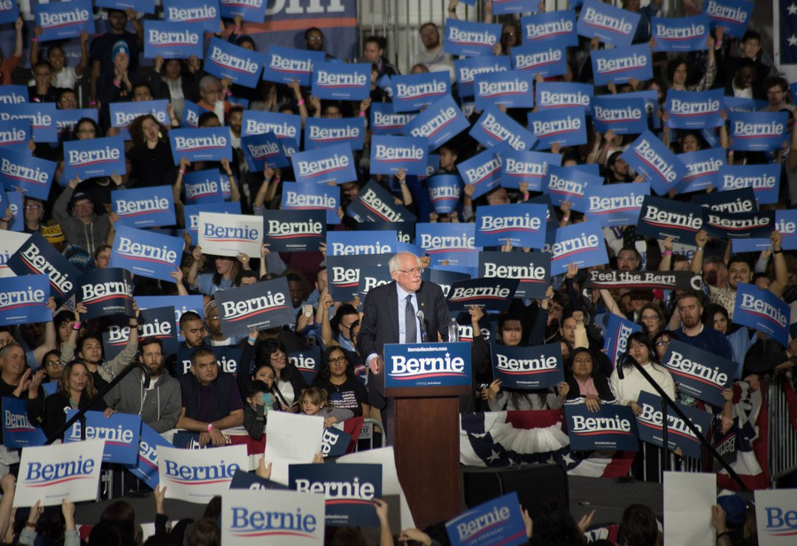 Sanders supporters at a rally hold 'Bernie' signs.