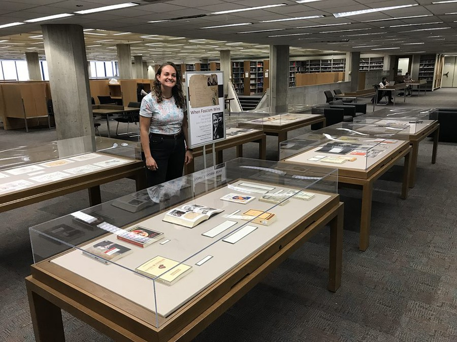 Second-year Maya Osman-Krinsky standing next to the exhibit they created at the Reg.