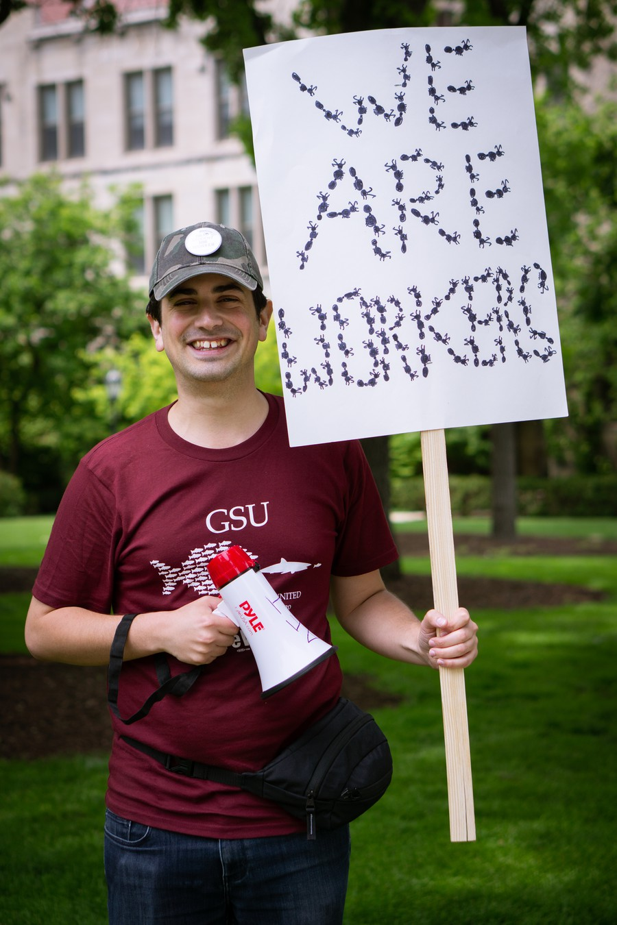 "PhD candidate in evolutionary biology Ben Blanchard holds a sign reading ""We Are Workers,"" spelled in ants."