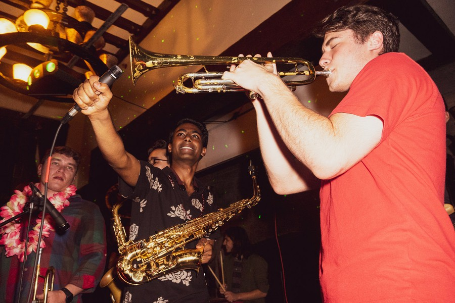 Members of UChicago's Dirt Red Brass Band perform at Alpha Delt fraternity.