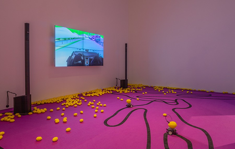 "Plastic lemons are scattered across the floor in front of bizarre animations in Young's installation, ""The highway is like a lion's mouth."""