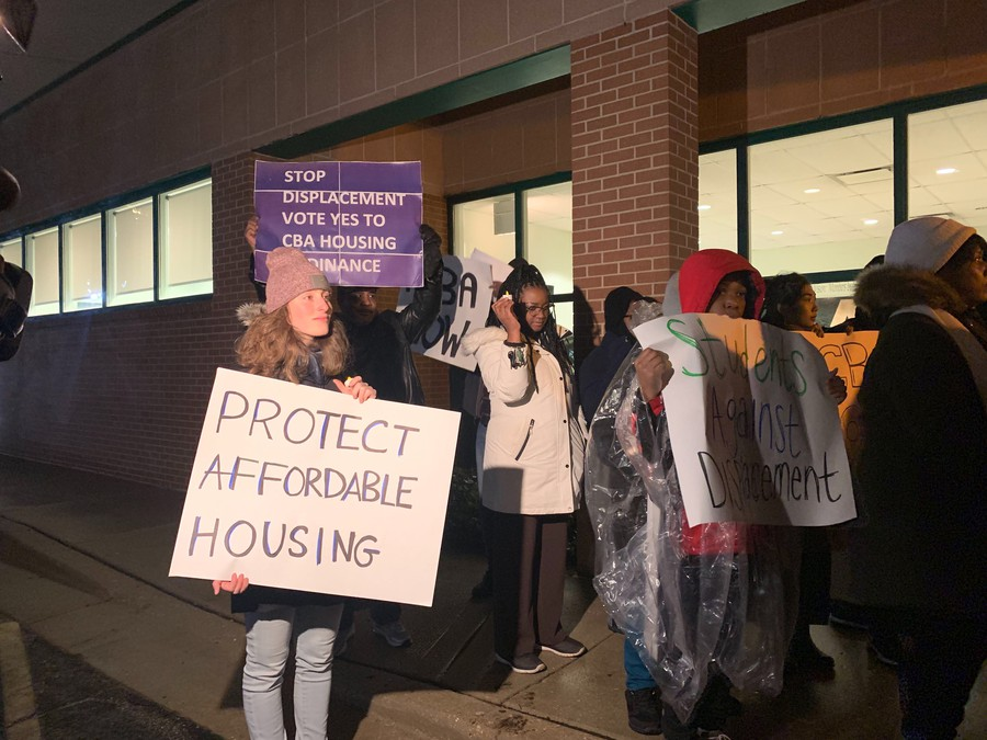 Organizers with the CBA Coalition protest outside a City affordable housing meeting.