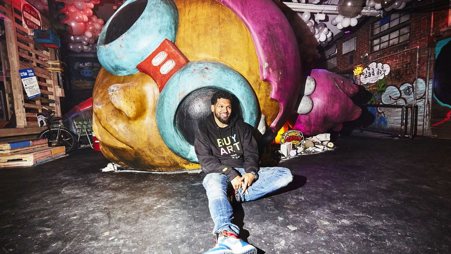 "Hebru Brantley sits in front of a massive Flyboy head in ""Nevermore Park,"" his immersive installation in Pilsen."