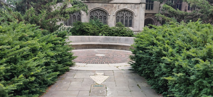 """The keystone from Douglas Hall at the Old University of Chicago set in the """"C Bench"""" outside Cobb Hall."""