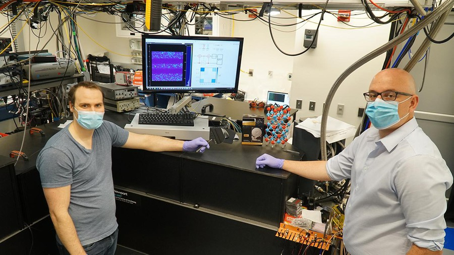 Researchers Alexandre Bourassa (left) and Chris Anderson (right) next to their quantum measurement instrumentation at the University of Chicago Pritzker School for Molecular Engineering.
