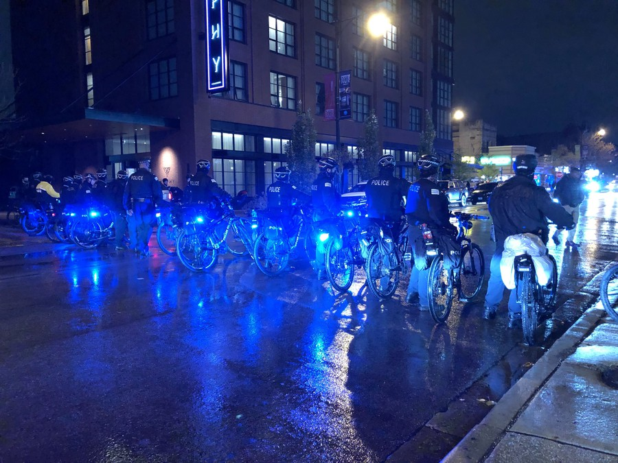 Police form a bicycle line as they corral a group of teens west on 53rd St.