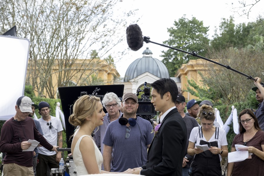 "Co-stars Jessica Rothe and Harry Shum Jr. film the wedding scene of ""All My Life"", surrounded by cast and crew."