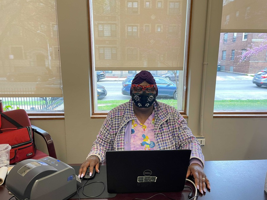 Carrol J. Banks, a coordinator for UChicago's COVID-19 testing program, sits at the check-in desk at the Woodlawn Social Services Center Depot.